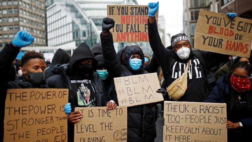 Des manifestants masqués brandissent des pancartes dénonçant le racisme, le poing en l'air.
