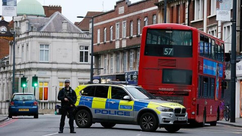 Un policier tient une arme près d'une auto-patrouille et un autobus.
