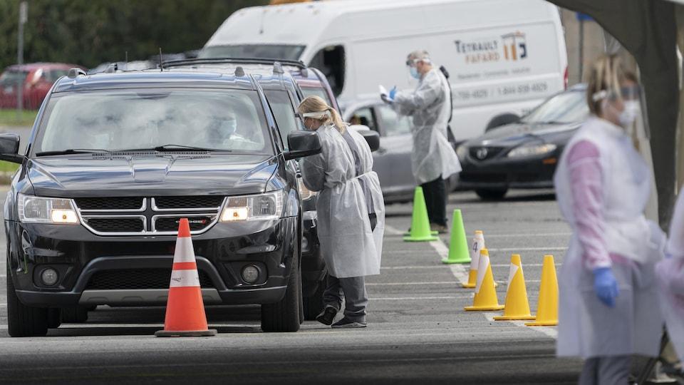 Des préposés font passer des tests de dépistage de la COVID-19 à des automobilistes.