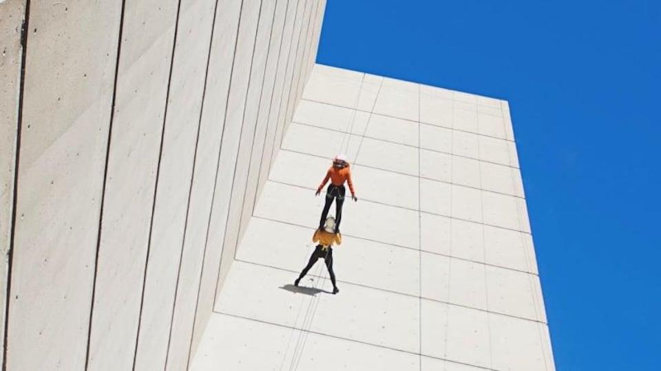 Deux acrobates de la compagnie Look-up Arts aériens qui sont retenus par des fils sur la façade d'un édifice