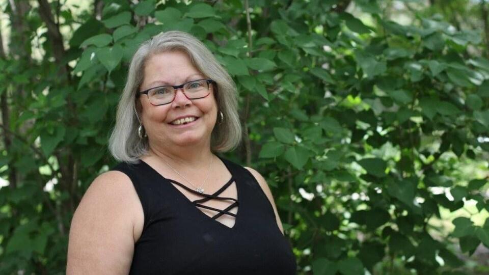 Une femme aux cheveux grisonnant et portant des lunettes sourit à la caméra.