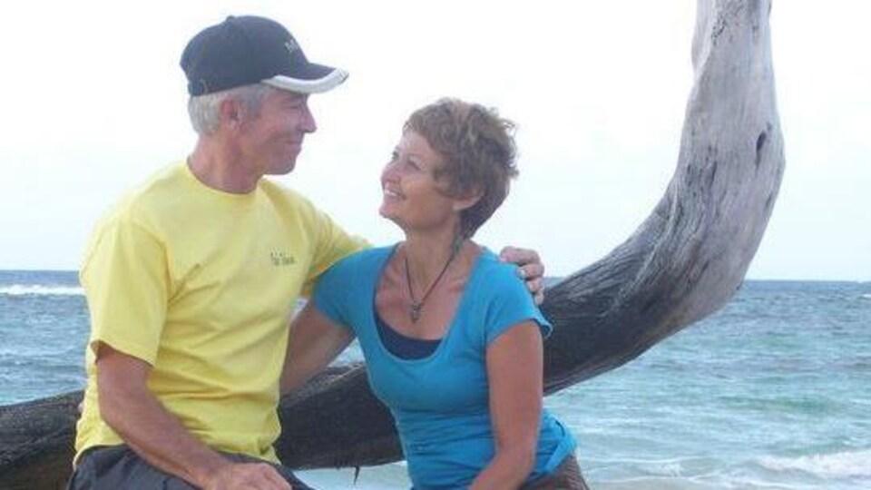 Lorretta Hughes (à droite) et son mari se regardent assis sur un arbre sur une plage avec la mer derrière eux.