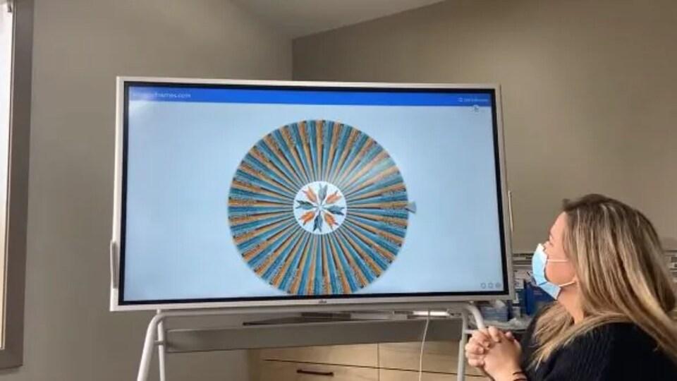 Une femme regarde le tirage sur un écran.
