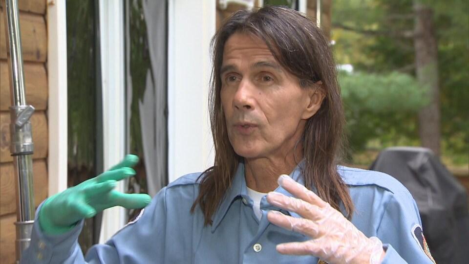 Lothaire Bluteau s'adresse à la caméra lors d'une entrevue extérieure devant une maison en bois.