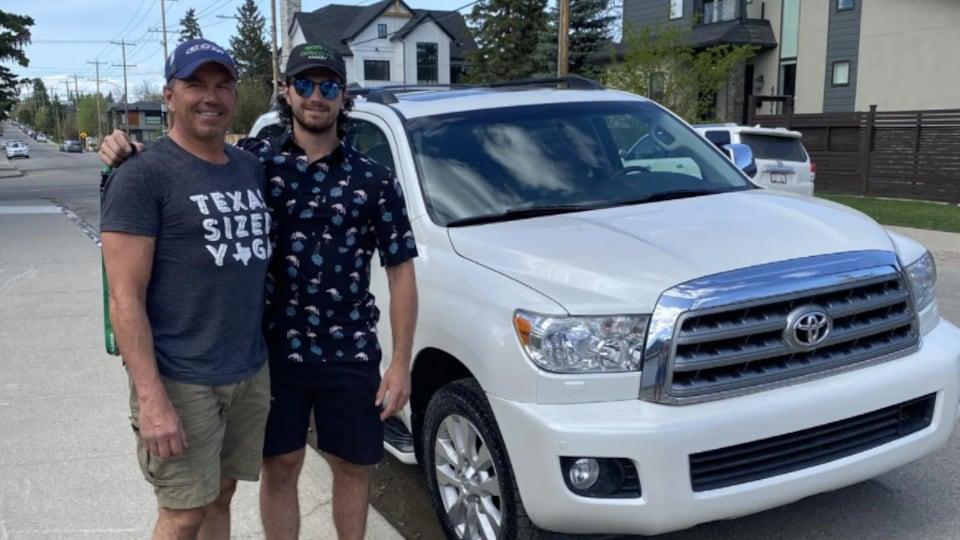 Lou Jamernik et son fils Louis posent devant une voiture.