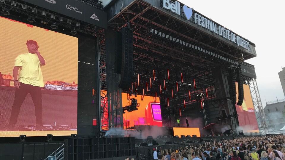 Une scène avec des écrans et une foule à l'avant
