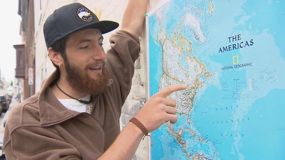 Louis Astoux montre du doigt le Québec sur une carte des amériques