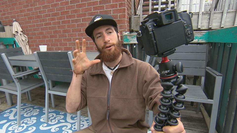 Louis Astoux brandit une caméra attachée à un trépied.