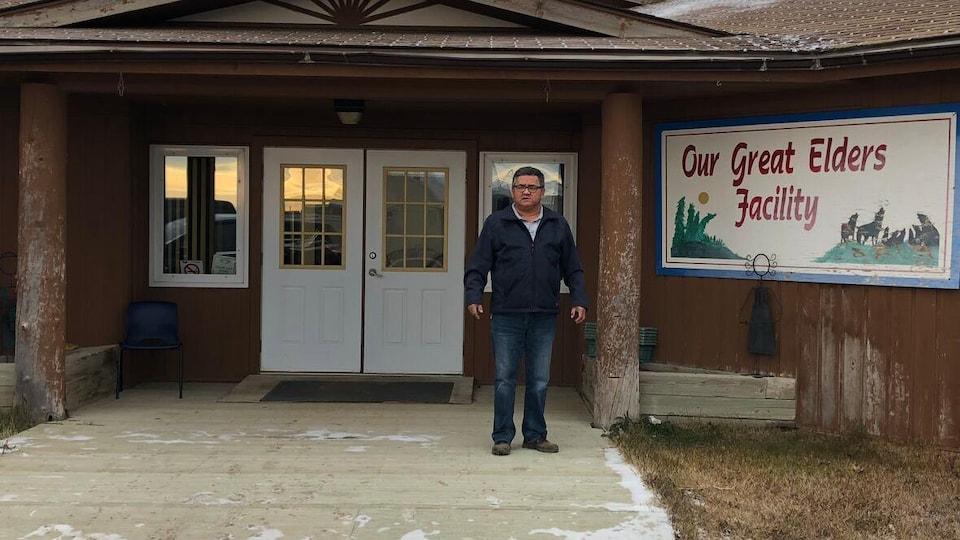 Un homme se tient devant un bâtiment.