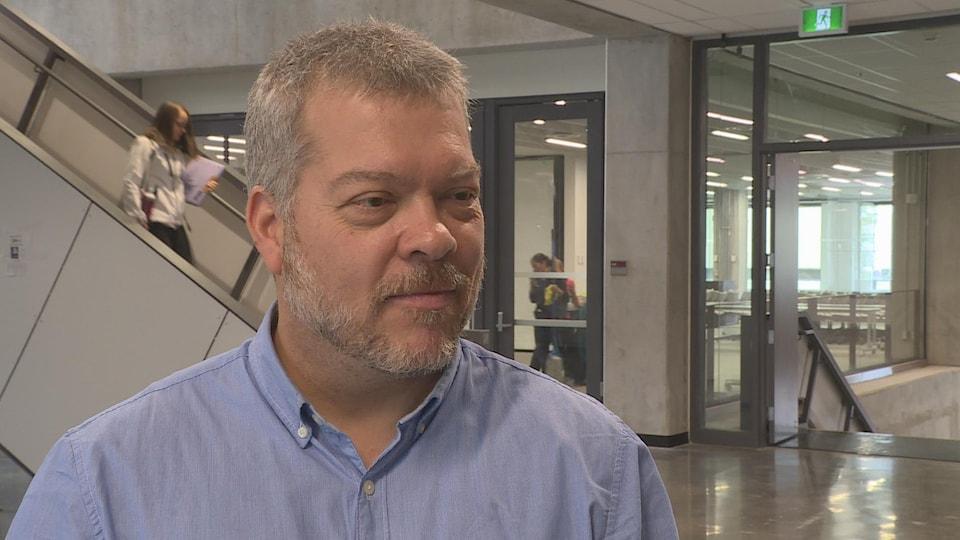 Louis Barriault en entrevue à la caméra de Radio-Canada devant un escalier dans un édifice.