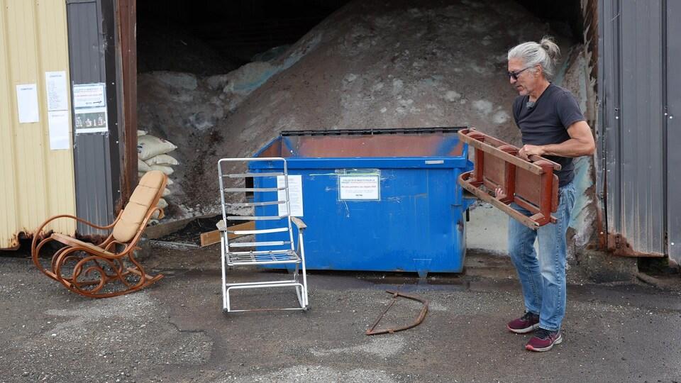 Louis Couturier manipule une luge devant un conteneur.