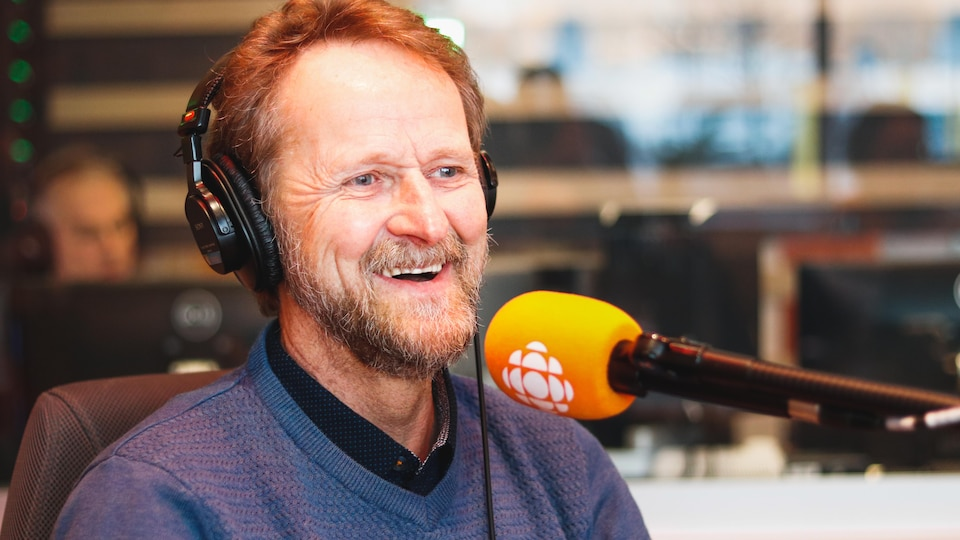 Un homme barbu et souriant parle à un micro dans un stuidio.