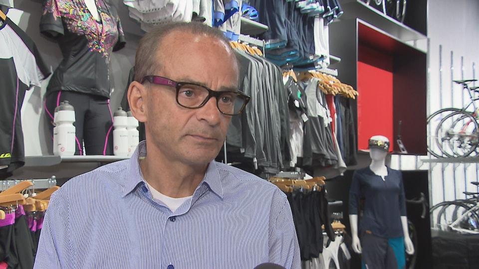 Louis Garneau accorde une entrevue à Radio-Canada au magasin de son entreprise à Saint-Augustin-de-Desmaures. On aperçoit des vêtements de sport et des vélos à l'arrière-plan.