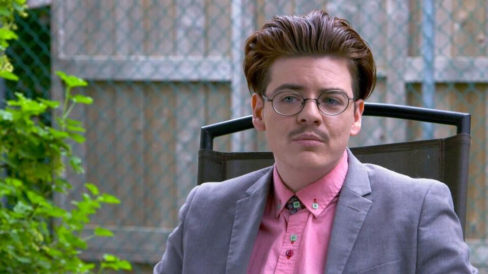 Un homme portant des lunettes et la moustache est assis sur une chaise, dans une cour extérieure.