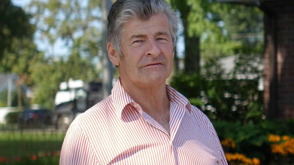 Louis Marcotte sourit, il porte une chemise blanche avec des lignes roses.
