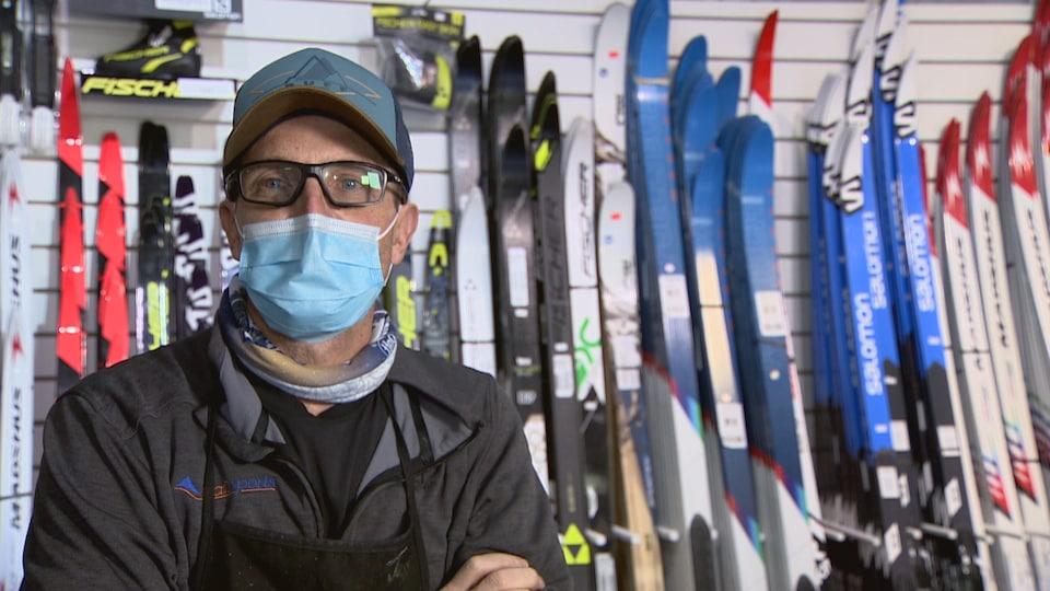 Louis Marino, devant un étalage de skis.