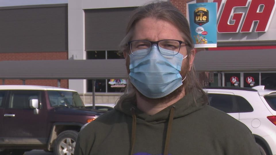 Un homme debout dehors avec un masque