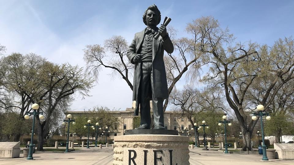 Sur une estrade sur laquelle est écrit Riel, un homme avec une moustache, bien vêtu et portant la ceinture fléchée, brandit fermement un papier.