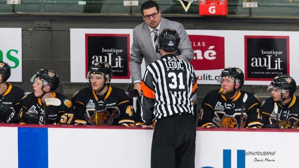 Un homme en complet sur le banc des joueurs pendant une partie de hockey.