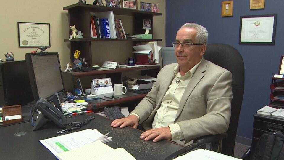 Louis Tétrault, assis dans son bureau. Devant lui, des cahiers et des feuilles, à sa droite, un ordinateur.