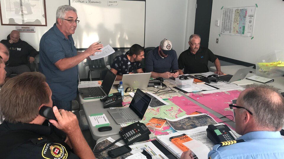 Le coordinateur des mesures d'urgence de la municipalité rurale de la Broquerie, Louis Tétrault (debout à gauche), le conseil municipal ainsi qu'une équipe de résidents bénévoles.