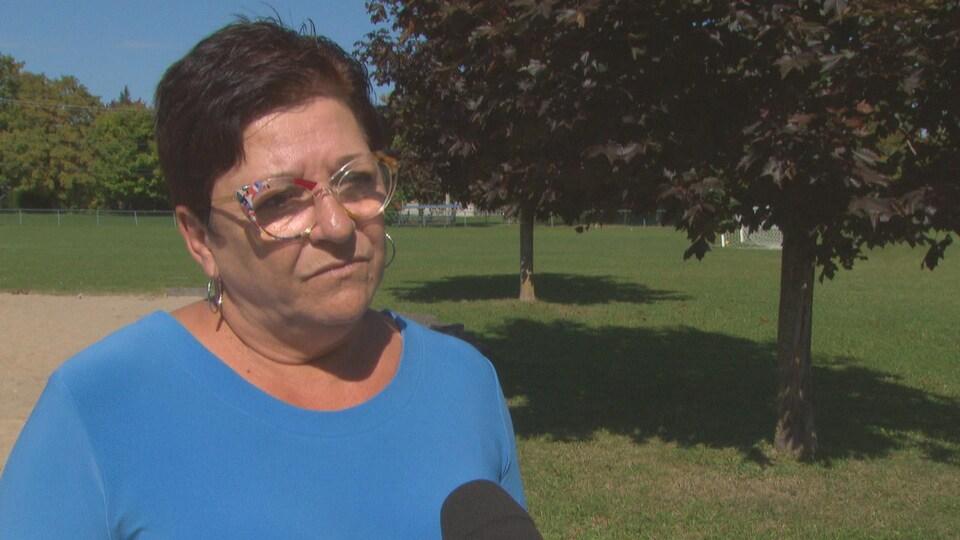 Louise Boudrias en entrevue dans un parc.
