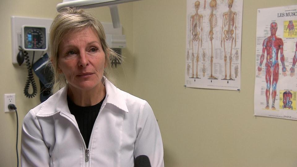 La Dre Louise Caron (plan rapproché) dans un cabinet de médecin. Elle porte une chemise blanche de médecin.