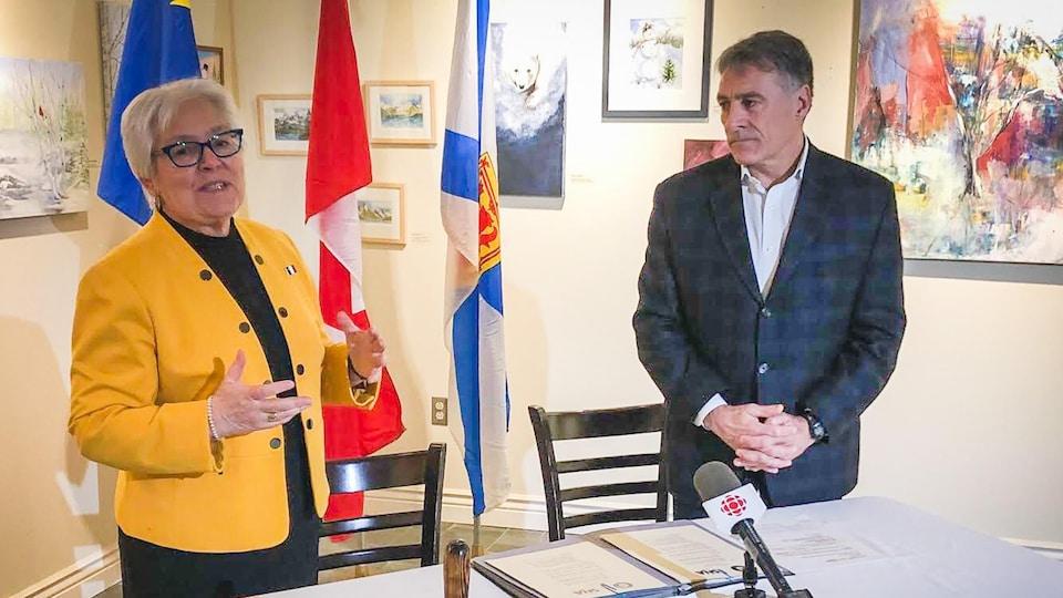 Louise Imbeault et Allister Surette derrière une table avec une nappe sur laquelle sont posés des micros de journalistes et devant des drapeaux.