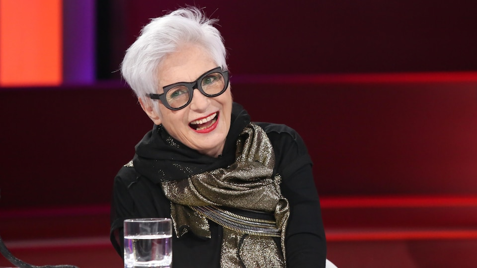 La femme aux cheveux blancs et lunettes noires rit.