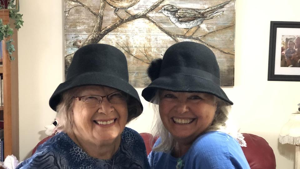 Deux femmes avec un chapeau qui sourient.