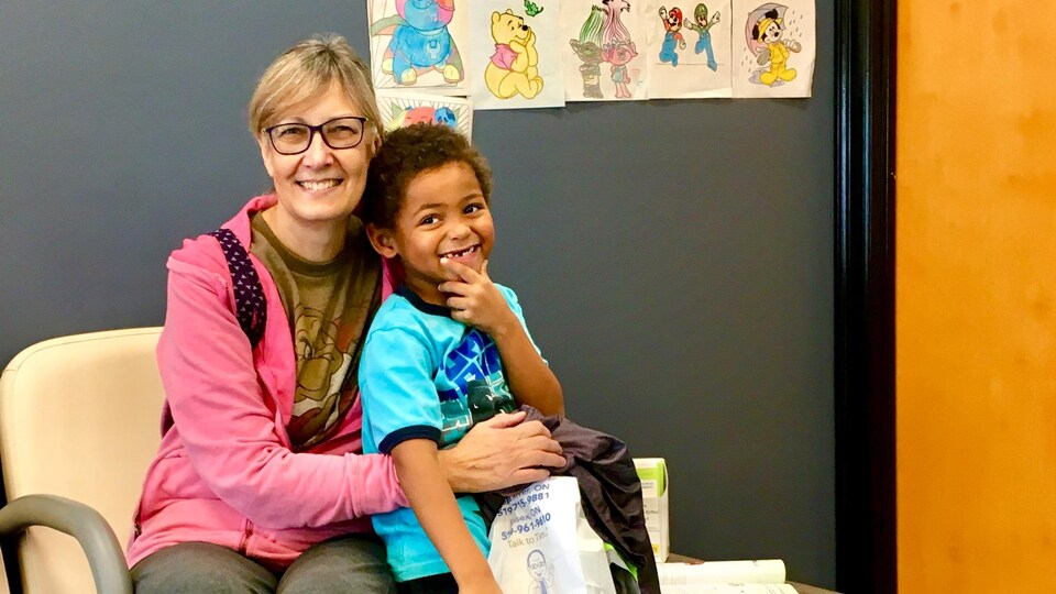 Une femme et son fils sourient.