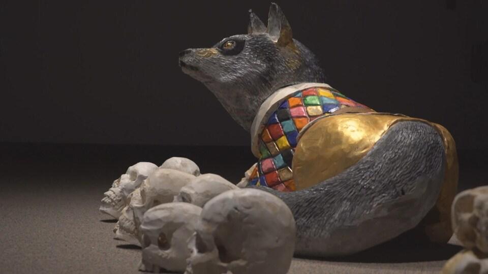 Un loup en or avec des têtes de mort autour.