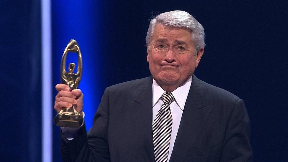 Michel Louvain tient un trophée dans la main droite.