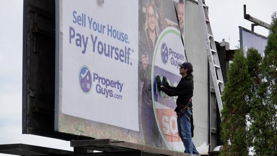 Un travailleur installe une publicité de propertyguys.com sur un grand panneau