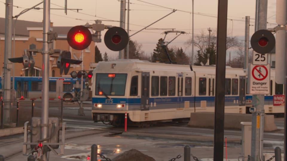 une intersection avec des feux rouges allumés et un train léger à l'arrêt en attendant de passer