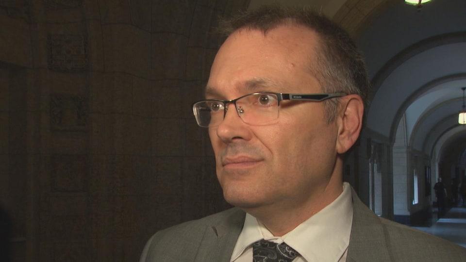 Le député Berthold donne une entrevue dans les couloirs du parlement.