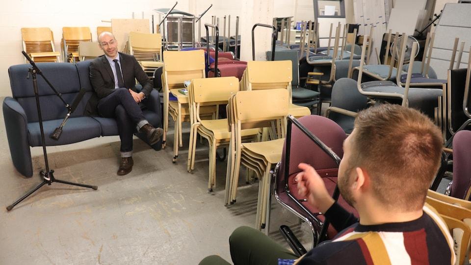 Le professeur en management de l'Université Laval, Luc Bres, au travers de chaises empilées dans un entrepôt.