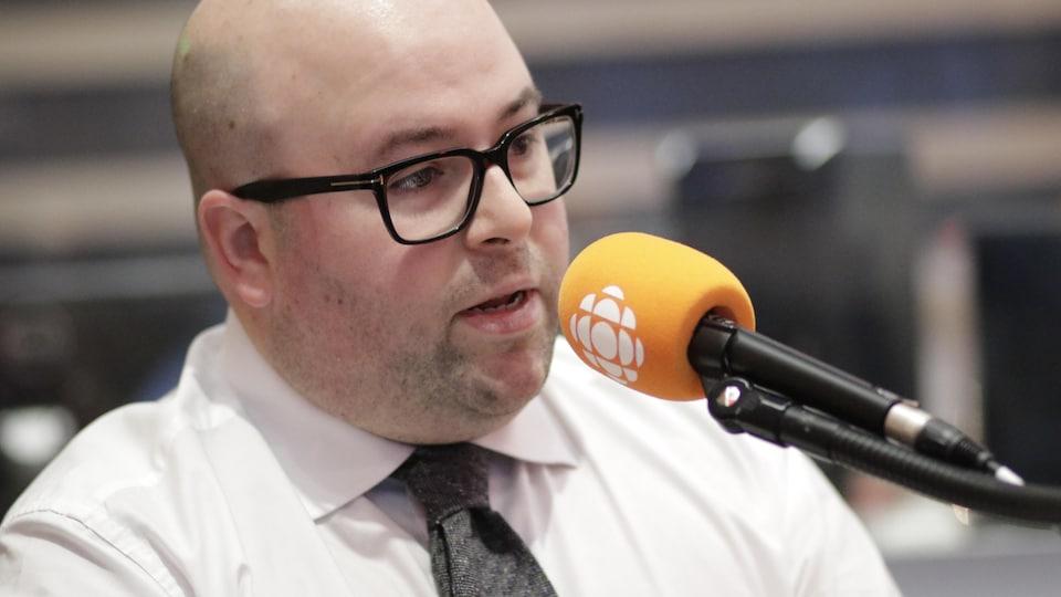 Une homme portant des lunettes parle au micro.
