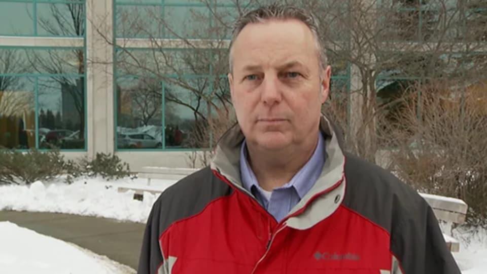 Luc Gagné pose pour la caméra à l'extérieur de l'hôtel de ville d'Ottawa en hiver.