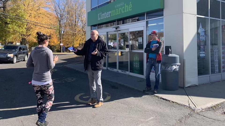 Luc Massé qui distribue un dépliant à l'entrée d'une épicerie de Saint-Boniface.