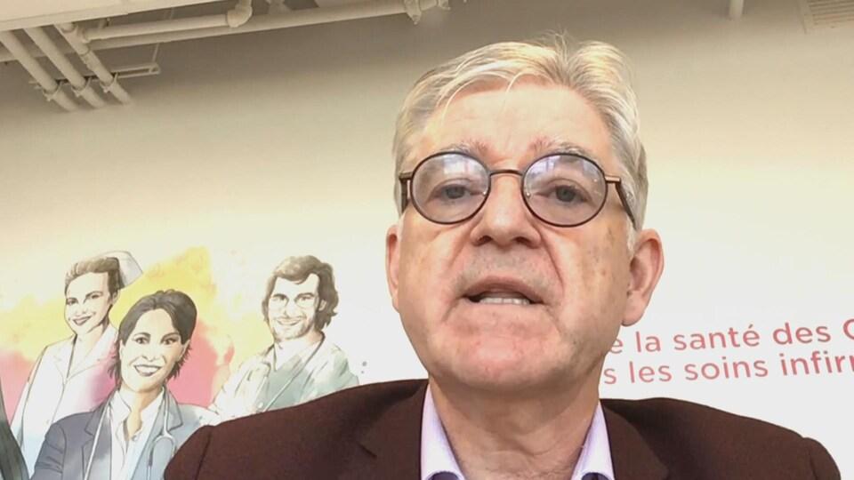 Un homme portant des lunettes devant un écran.