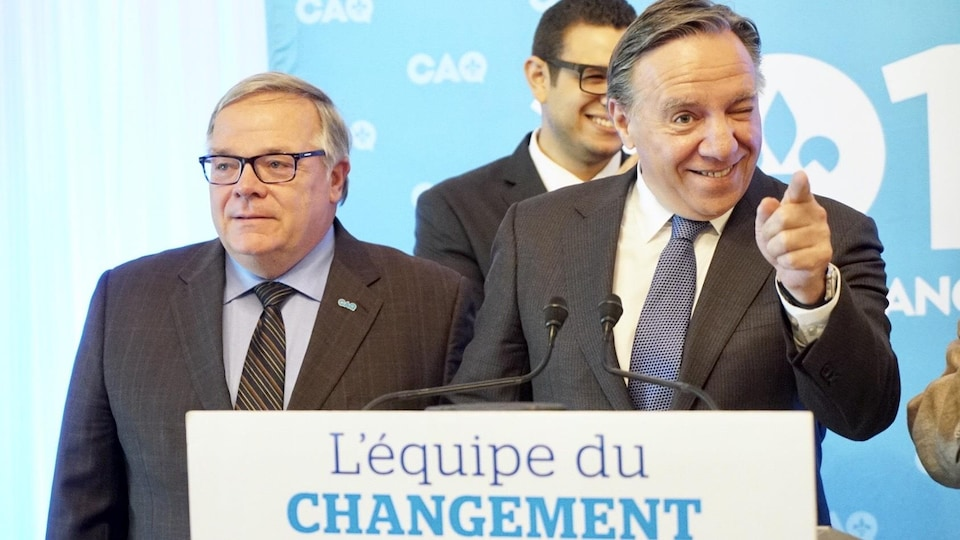Luc Provençal et François Legault lors d'un point de presse. Sur la photo, on aperçoit le chef de la CAQ faire un clin d'œil en pointant le doigt vers une personne de l'assistance.