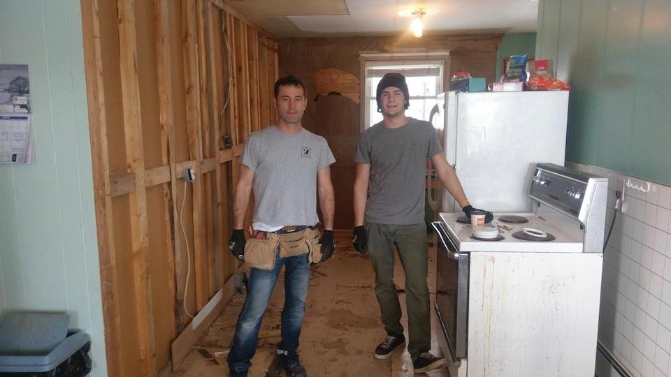 Un père et son fils dans une cuisine en travaux.