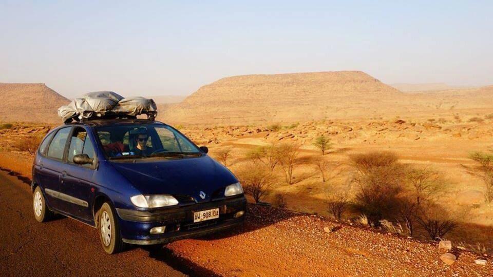 Une voiture bleue sur le bord de la route dans un lieu désertique.