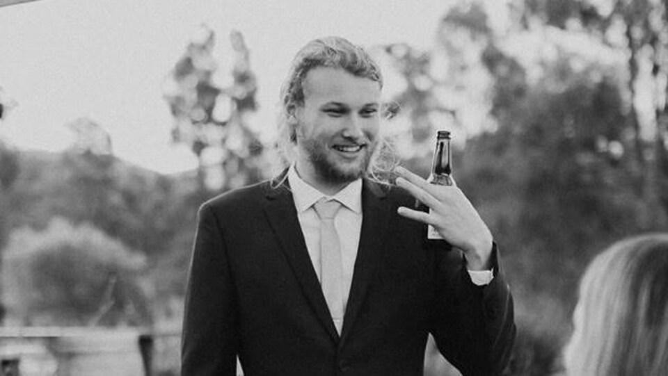 Photo en noir et blanc de Lucas Fowler souriant en costume cravate.