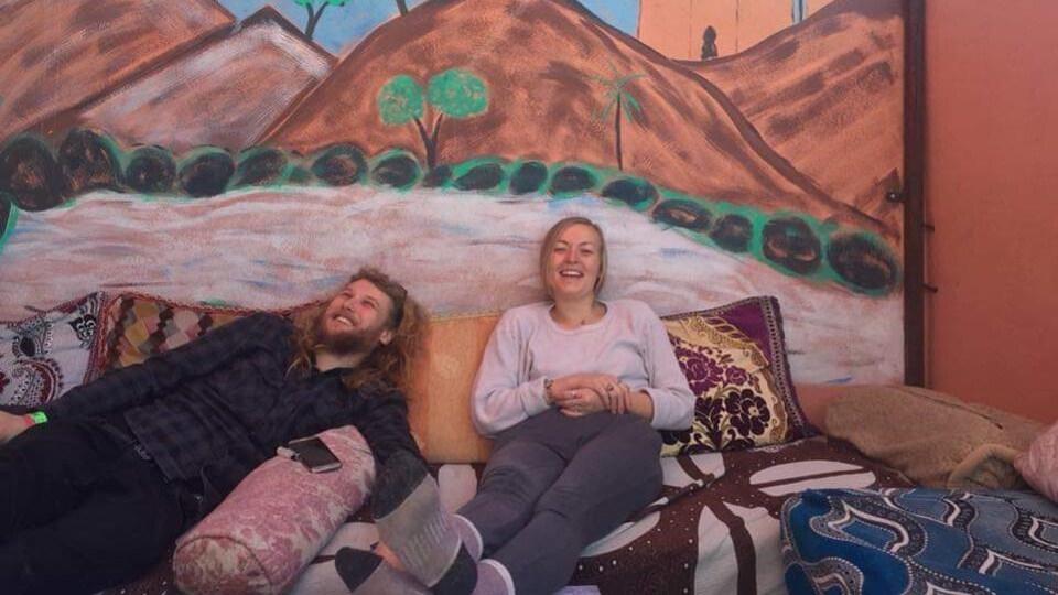 Lucas Fowler et Chynna Deese souriants, assis sur des coussins dans un endroit exotique.