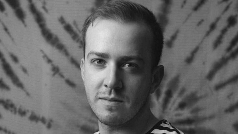 Un jeune homme photographié en studio.
