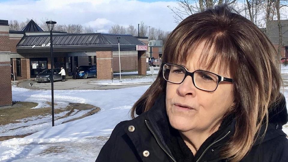 Une femme devant un hôpital