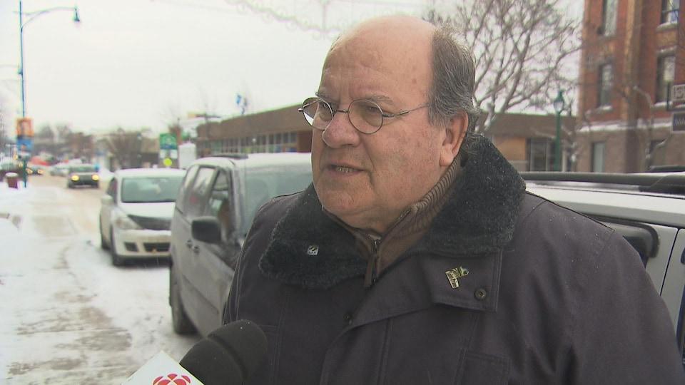 Lucien Boivin en position d'entrevue au micro de Radio-Canada.