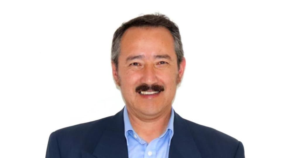 Le candidat aux élections fédérales porte une moustache et sourit à la caméra.